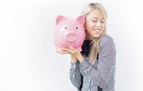 Happy woman holding pink piggy bank